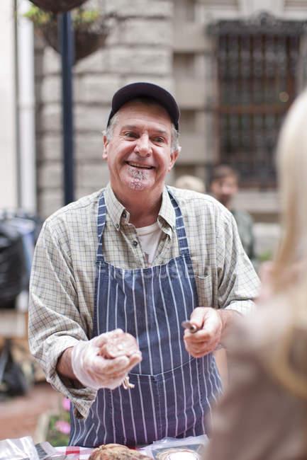 Чоловік продає ковбаса на міський ринок — стокове фото