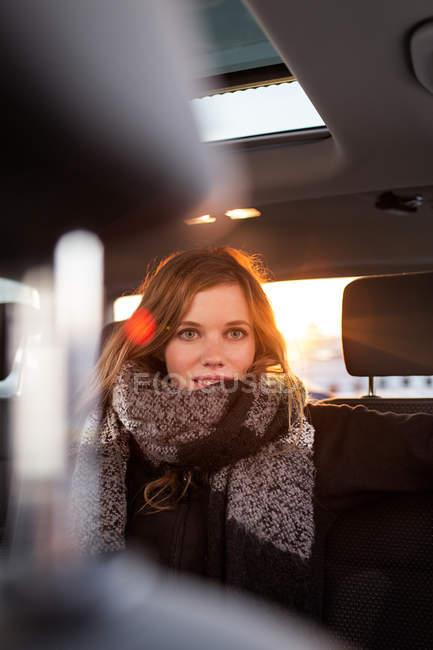 Mulher sentada no banco de trás do carro — Fotografia de Stock