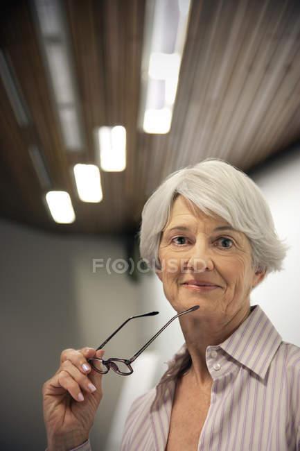 Portrait of a senior woman holding glasses — Stock Photo