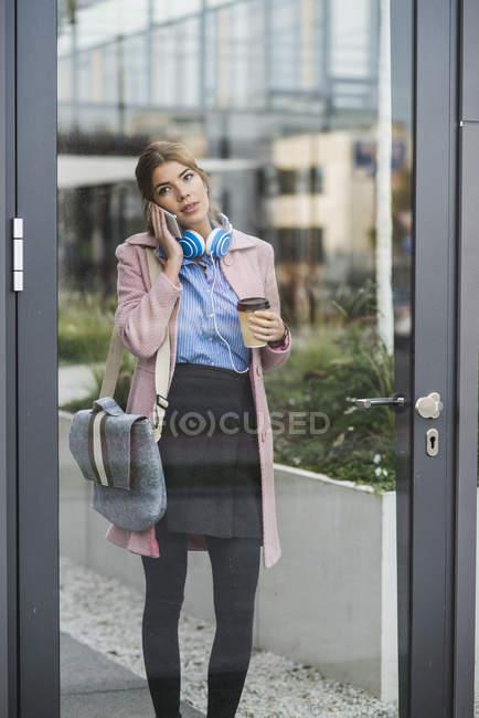 Jovem no celular segurando café para ir — Fotografia de Stock