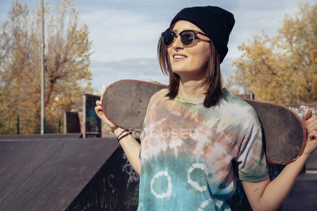 Smiling young woman holding skateboard at skatepark — Stock Photo