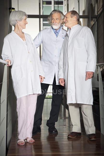 Трое выпускников в лабораторных халатах в университете — стоковое фото