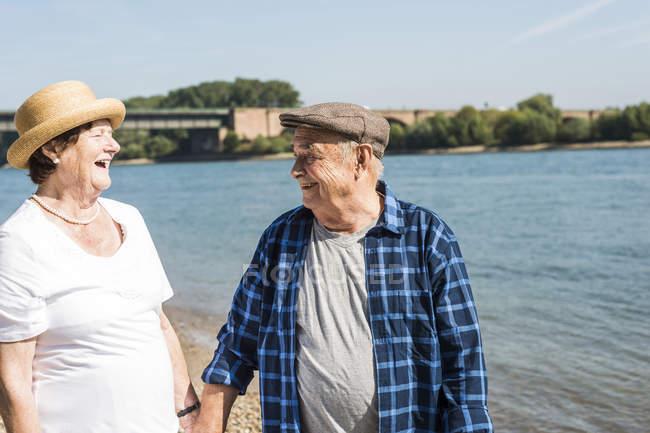 Старшая пара отдыхает на берегу реки — стоковое фото