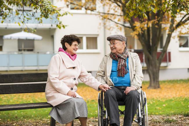 Senior woman sitting on bench next to husband in wheelchair — Stock Photo