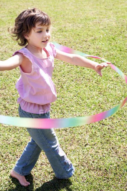 Petite fille jouer avec hula-hoop dans le jardin — Photo de stock