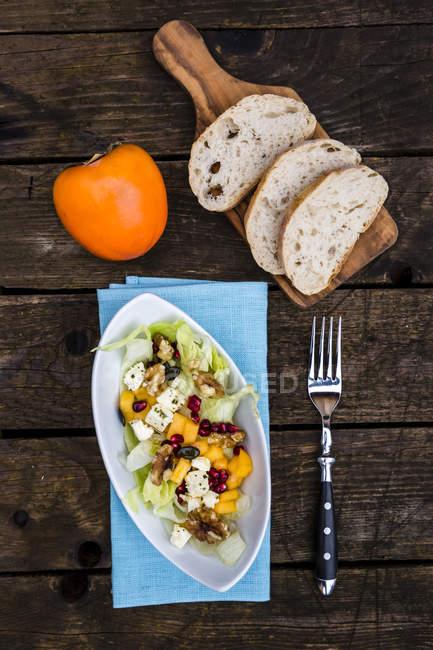 Осенний салат с Каки, сыр фета, салат Айсберг, семена тыквы, гранат и грецкими орехами — стоковое фото