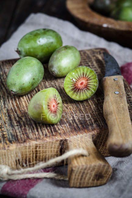 Sliced and whole mini kiwis and a kitchen knife on wooden chopping board — Stock Photo