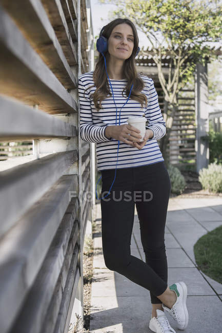 Woman with coffee hearing music — Stock Photo