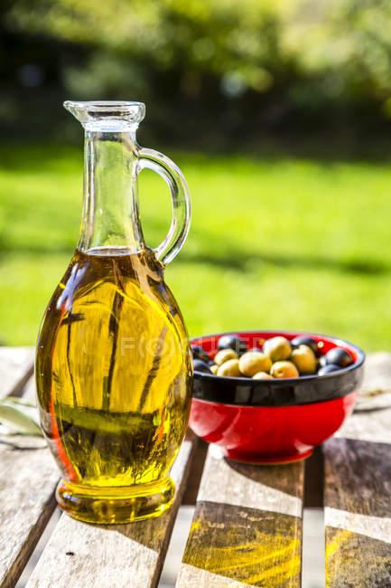 Bol aux olives vertes et noires et carafe d'huile d'olive — Photo de stock