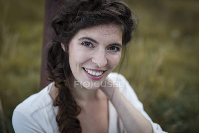 Smiling woman with braid looking at camera — Stock Photo