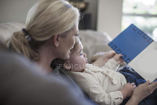 Мать и девочка дома смотрят на книгу — стоковое фото
