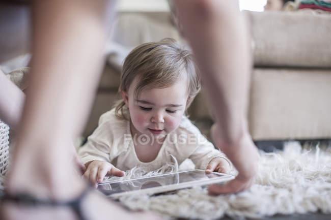 Дівчинку вдома лежить на підлозі з цифровий планшетний — стокове фото