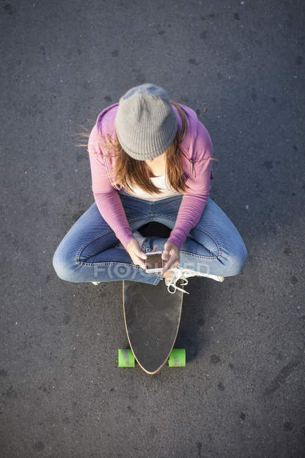 Teenage girl sitting on skateboard looking at cell phone — Stock Photo