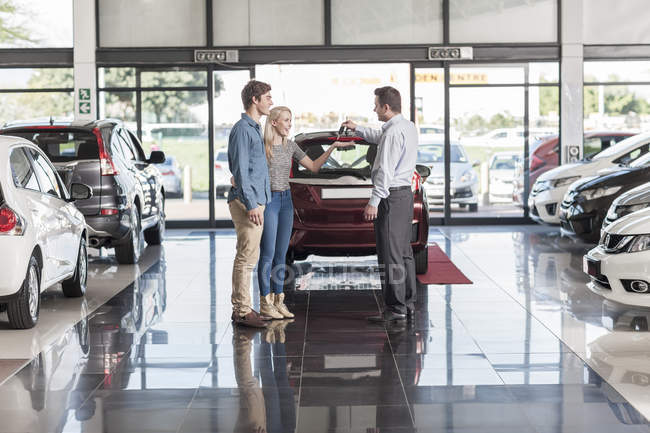 Car dealer giving key to clients — Stock Photo