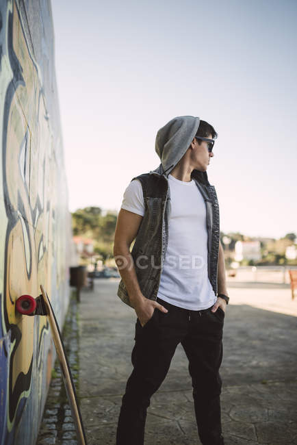 Young skateboarder with cool attitude standing outdoors — Stock Photo