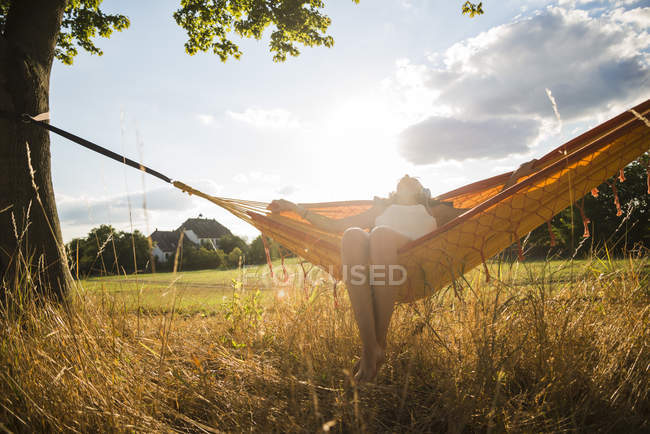 Woman with headphones lying in a hammock relaxing in nature — Stock Photo