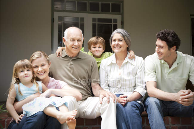 Group picture of three generations family sitting on the terrace — Stock Photo