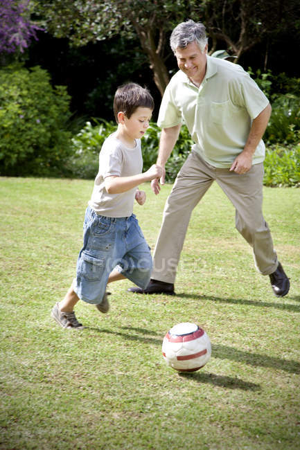 Little boy playing soccer with his grandfather — Stock Photo