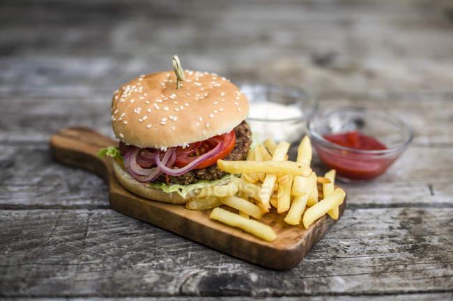 Hamburguesa casera con lechuga, carne, tomate, cebolla y papas fritas en la tabla de picar - foto de stock