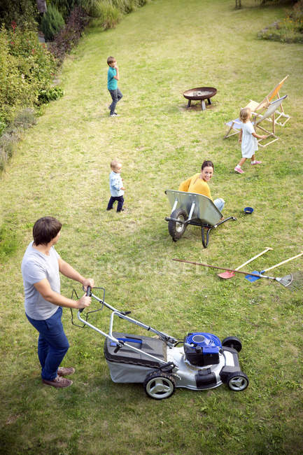[Image: focused_178097252-stock-photo-father-mow...family.jpg]