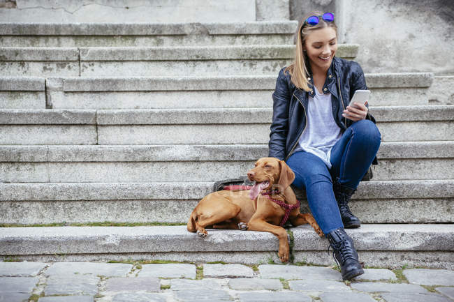 Mulher sorridente com smartphone sentado além do seu cão nas escadas — Fotografia de Stock