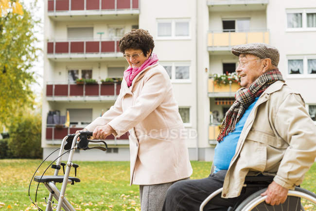 Senior woman with wheeled walker and senior man in wheelchair outdoors in autumn — Stock Photo