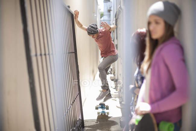 Jeune homme fait un tour de planche à roulettes dans un lieu de passage — Photo de stock