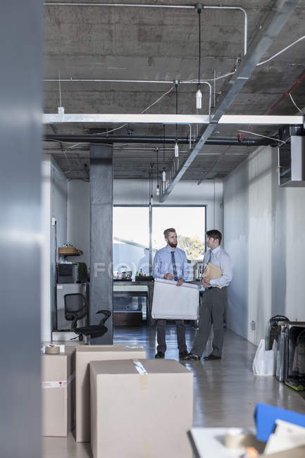 Two businessmen standing and talking in new office — Stock Photo