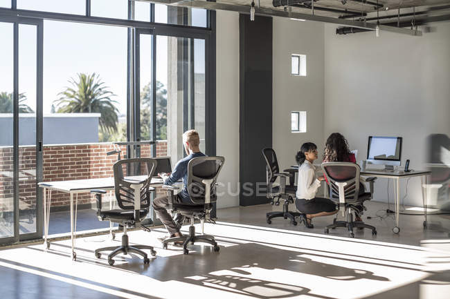 Young professionals working in open office — Stock Photo