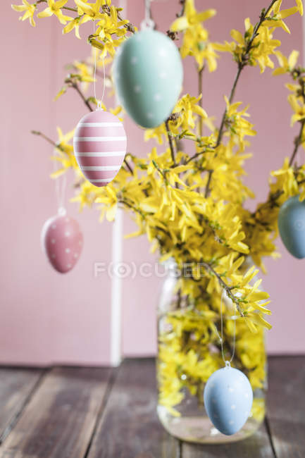 Bunch of Forsythia and colorful Easter eggs — Stock Photo