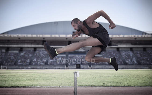 Athlete jumping over hurdle outdoors — Stock Photo