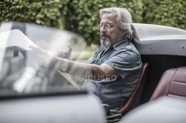 Homem sênior no carro esportivo, olhando para a lista de verificação bebendo limonada — Fotografia de Stock
