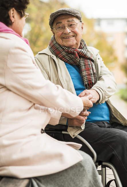 Senior homme en fauteuil roulant tenant la main avec sa femme sur le banc — Photo de stock