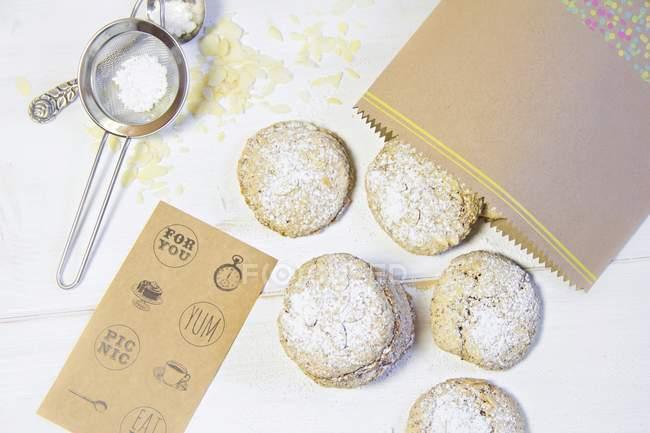 Vista superior de italianas galletas de almendra con bolsa de papel - foto de stock