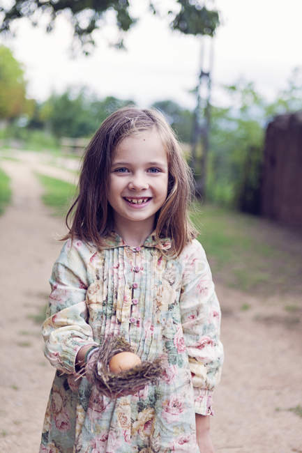 Smiling girl holding an egg in a nest — Stock Photo