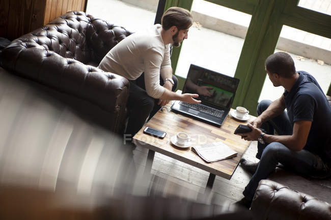 Two men with laptop sitting on couch in a lounge — Stock Photo