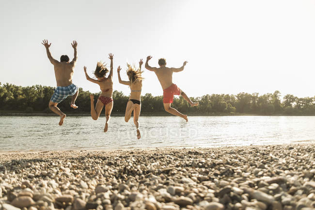 Happy friends jumping into river on beach — Stock Photo