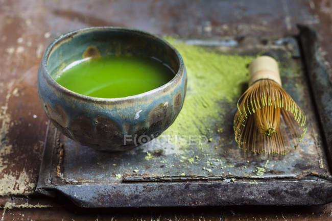 Closeup view of chawan of matcha tea and whisk — Stock Photo