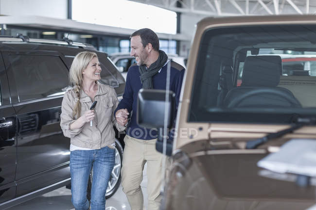 Happy couple at car dealership hand in hand at new car — Stock Photo