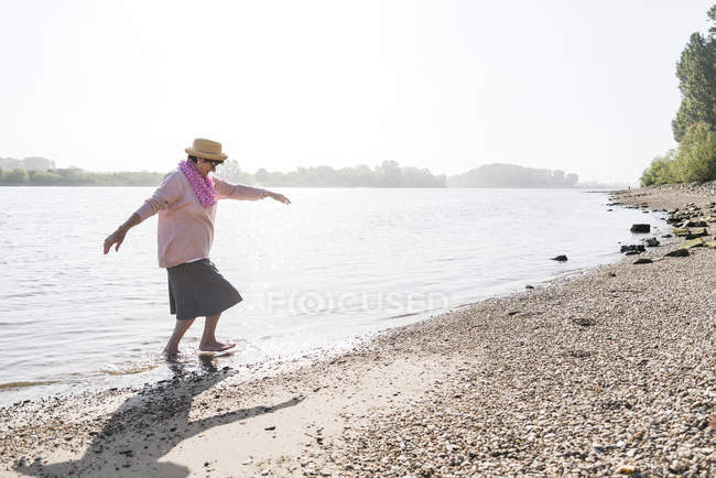 Germany, Ludwigshafen, senior woman walking out of Rhine River — Stock Photo