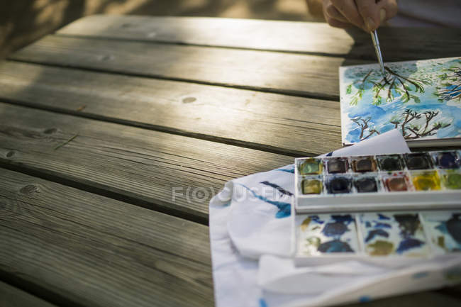 Woman painting on wooden table outdoors — Stock Photo