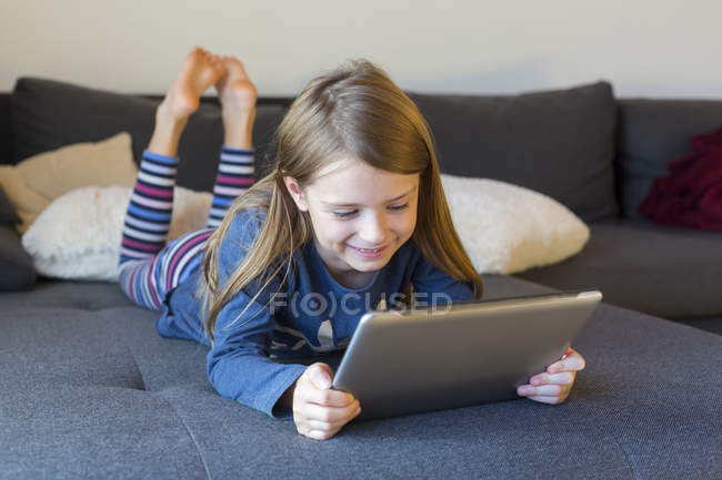 Smiling girl lying on the couch using digital tablet — Stock Photo