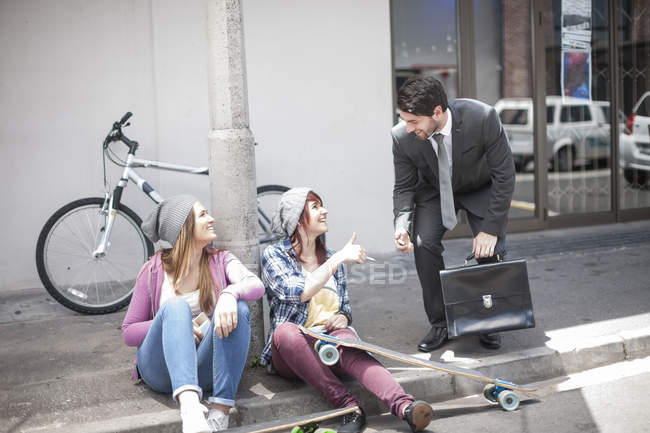 Businessman giving a lighter to two female friends on city street — Stock Photo