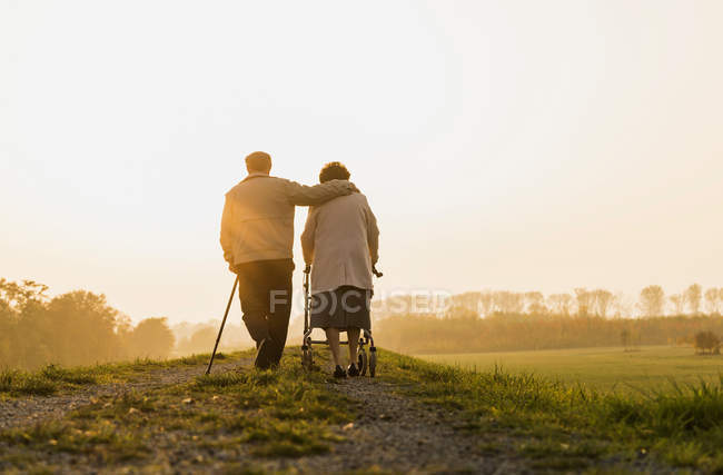 Senior couple walking with walking stick and wheeled walker in the nature — Stock Photo