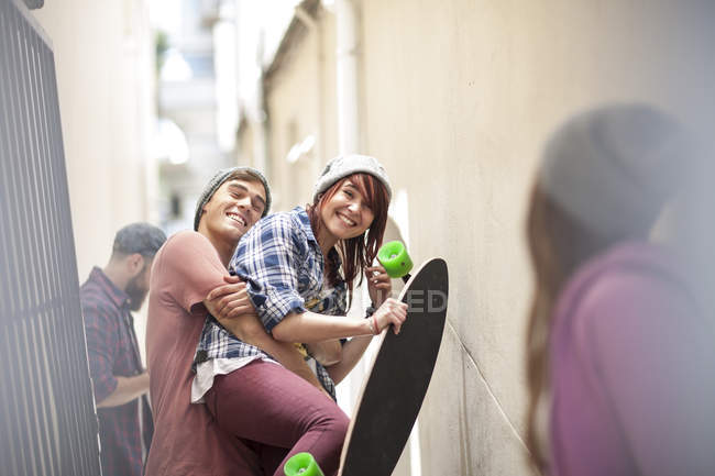 Friends with skateboard having fun in a passageway — Stock Photo