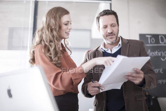 Dos colegas en la oficina discutiendo papeles - foto de stock