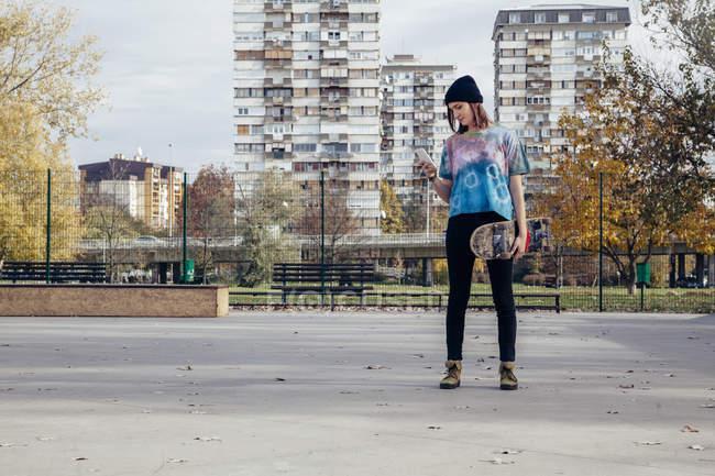 Jovem com skate olhando para o telefone celular — Fotografia de Stock