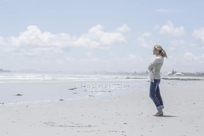 Mujer de pie en la playa mirando a la distancia - foto de stock