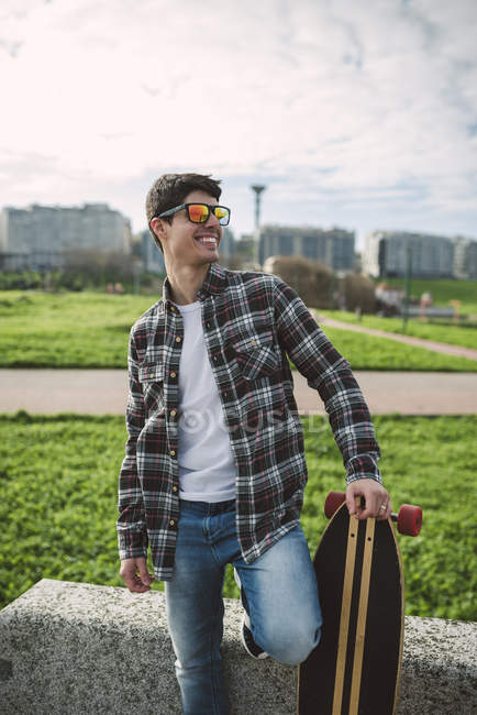 Smiling young man with longboard wearing mirrored  sunglasses — Stock Photo