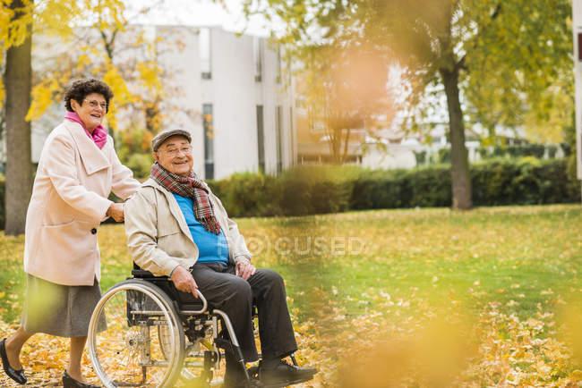 Seniorin schubst Mann im Rollstuhl — Stockfoto